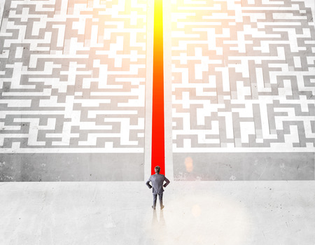 cut through the maze: Success concept with businessman and illuminated red path groing through maze on concrete ground