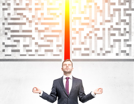 cut through the maze: Success concept with meditating businessman and illuminated red path groing through maze on concrete ground Stock Photo
