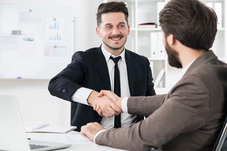 cerrando negocio: hombres de negocios alegres dándose la mano en el escritorio de la oficina moderna con ordenador portátil y otros artículos. Los empresarios cierran acuerdo de negocios