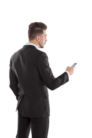 back view of man: Back view of young stylish businessman isolated on white background using smart phone