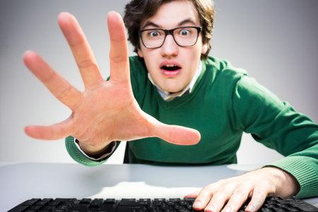 컴퓨터 키보드 책상에 앉아서 그 앞에 뭔가를 잡으려고 노력하는 놀라운 젊은 남자