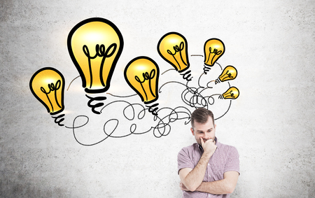 thoughtful: Idea concept with thoughtful casual man standing against concrete wall with lighbulb drawings Stock Photo