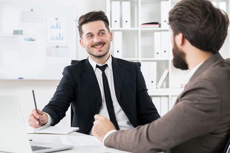 hardworking: Two bearded hardworking businessmen discussing something at modern office desk Stock Photo