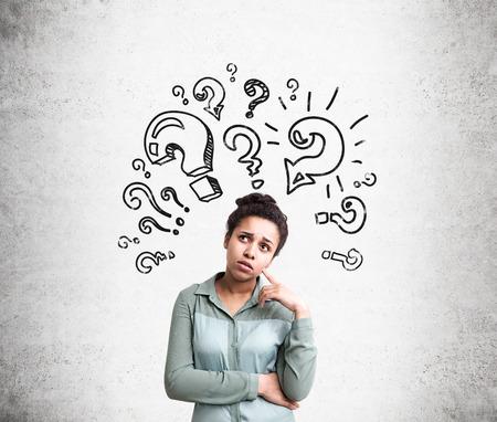 Confus femme afro-américaine en essayant de trouver des réponses à ses questions avec point d'interrogation croquis sur fond de béton