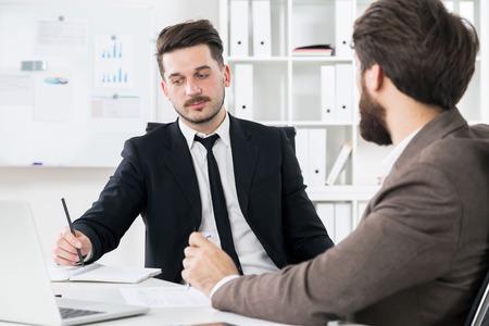 hardworking: Successful hardworking businessmen discussing something at modern office desk Stock Photo