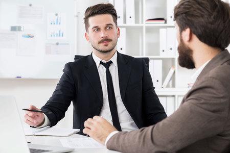 hardworking: Two handsome hardworking businessmen discussing something at modern office desk
