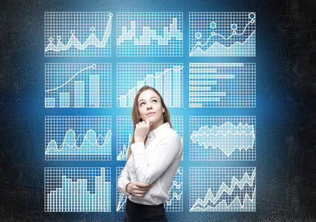 Thoughtful businesswoman standing against concrete wall with business charts on grid Stock Photo
