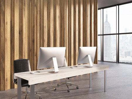 office window view: Side view of office interior with two computer monitors on wooden desktop, wall, concrete floor and window with New York city view. 3D Rendering Stock Photo