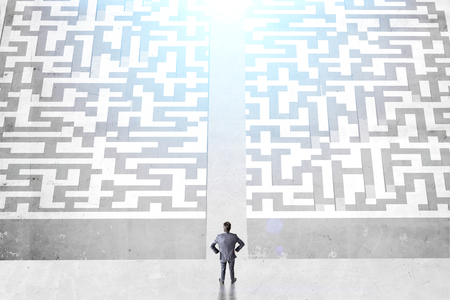 cut through the maze: Success concept with businessman and difficult maze divided into two parts on concrete ground