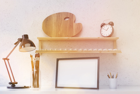 shelf: Front view of desktop with picture frame, pencils, brushes, lamp and wooden shelf with empty paint palette and alarm clock above on concrete wall background. Toned image. Mock up, 3D Rendering Stock Photo