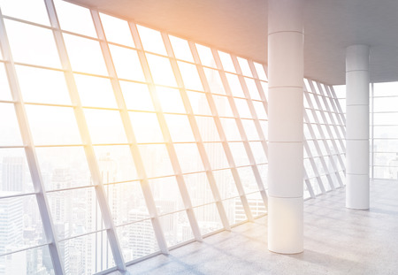 spacious: Empty spacious office interior with columns, concrete floor and panoramic framed windows with New York city view and sunlight. Toned image. 3D Rendering