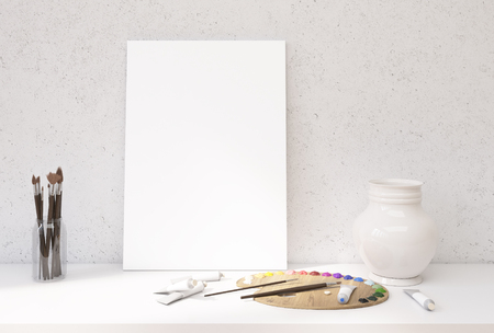 blank canvas: Front view of white desktop with blank canvas leaning on concrete wall, oil paint palette and tubes, decorative vase and set of brushes. Mock up, 3D Rendering Stock Photo