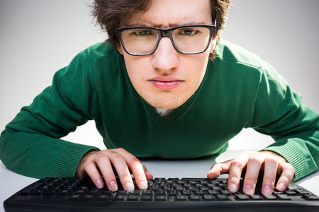 closely: Young man sitting at desk with hands on keyboard and looking closely at the camera Stock Photo
