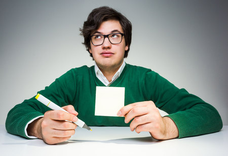 hand raising: Young man in green pullover sitting at white desk with blank paper sticker and marker in hand, raising eyebrows and looking up Stock Photo