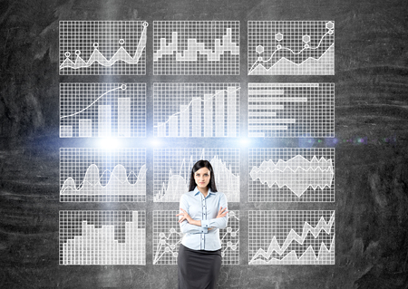 confident: Confident businesswoman standing against concrete wall with business charts on grid Stock Photo