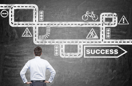 complex navigation: Businessman looking at road to success sketch on chalkboard background