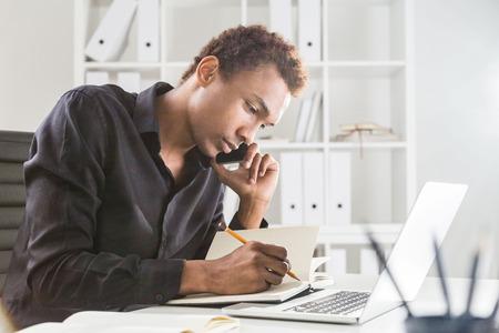 Zijaanzicht van geconcentreerde Afro-Amerikaanse zakenman met behulp van blocnote en laptop op kantoor desktop terwijl het hebben van een mobiel telefoongesprek. Boekenplank met documenten op de achtergrond