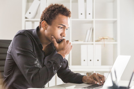 Doordachte zwarte zakenman werken op projectbasis op kantoor bureau met laptop en notitieblok. Boekenplank met documenten op de achtergrond