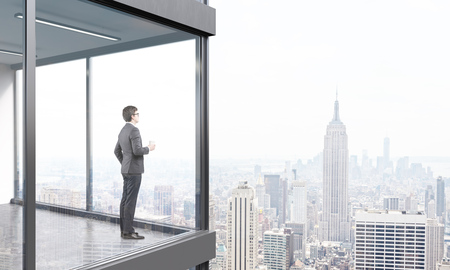 modern office interior: Young businessman standing on panoramic balcony looking at New York city. 3D Rendering