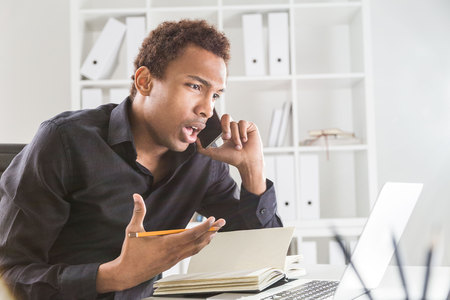 phonecall: Side view of attractive african american businessman using notepad and laptop on office desktop while explaining something passionately over phone. Bookshelf with documents in the background