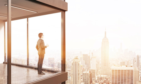 penthouse: Young businessman standing on panoramic balcony looking at New York city. Toned image. 3D Rendering