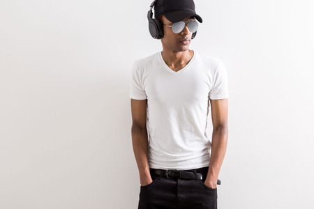 Young african american guy in cap and sunglasses listening to music with headphones on light background