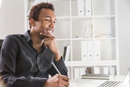 Buon uomo d'affari nero che lavora al progetto sulla scrivania con il computer portatile e un blocco note. Libreria con i documenti in background Archivio Fotografico