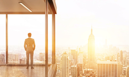 penthouse: Back view of young businessman standing on panoramic balcony looking at New York city. Toned image. 3D Rendering