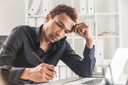 Handsome black businessman working on project on office desk with laptop and notepad. Bookshelf with documents in the background
