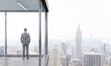 Back view of young businessman standing on panoramic balcony looking at New York city. 3D Rendering