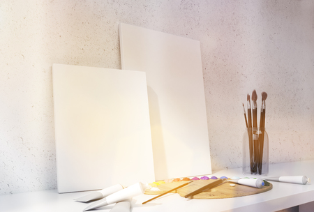 blank canvas: Two blank canvas, oil paint palette and brushes on white desktop and concrete wall background. Toned image. Mock up, 3D Rendering Stock Photo