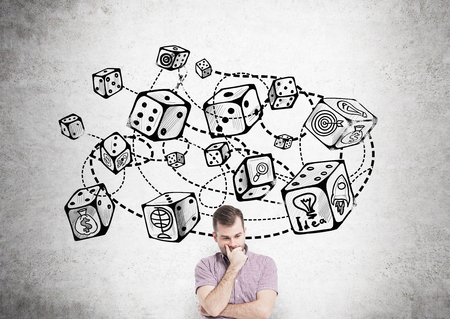 probability: Thoughtful young man standing against concrete wall with connected dice sketch. Game and probability theory Stock Photo