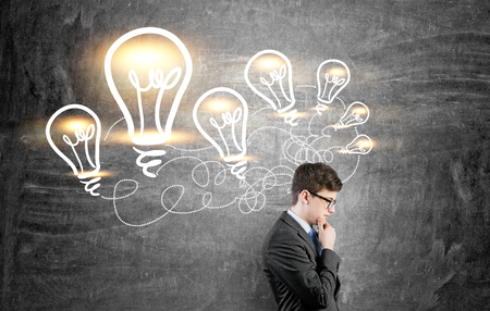 Idea concept with thoughtful businessman standing against chalkboard with illuminated lightbulb sketches Stock Photo