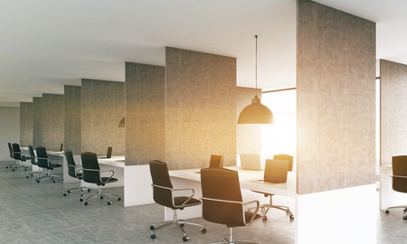 ceiling design: Side view of concrete coworking office interior design with laptops on workplaces, ceiling lamps and sunlight. 3D Rendering Stock Photo