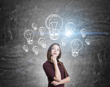 thoughtful: Idea concept with thoughtful girl and illuminated light bulb sketches on chalkboard background