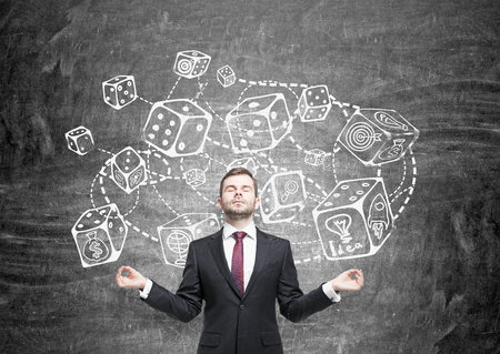 probability: Meditating businessman standing against chalkboard with connected dice sketch. Game and probability theory Stock Photo