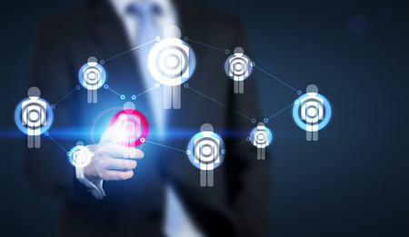 targeting: Targeting concept with businessman pointing at red dartboard on human icon network