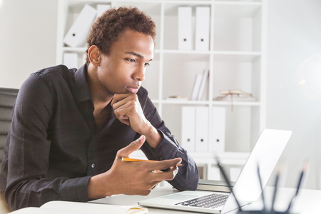 Pensive black businessman working on project on office desk with laptop and notepad. Bookshelf with documents in the background Banque d'images