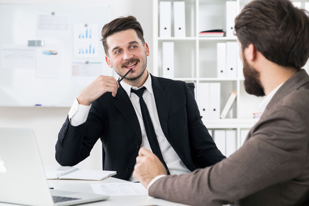 hardworking: Two attractive hardworking businessmen discussing something at modern office desk