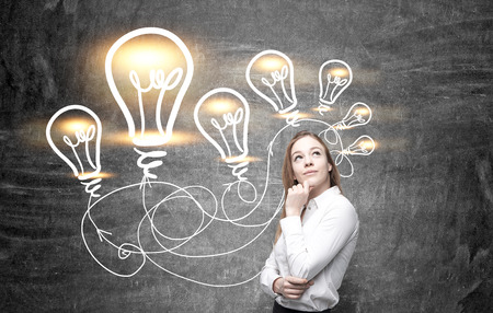thoughtful: Idea concept with thoughtful businesswoman and illuminated lightbulb sketches on chalkboard background Stock Photo