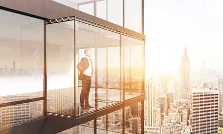 penthouse: Thoughtful businessman looking into the distance from empty balcony interior on New York city background with sunlight. 3D Rendering