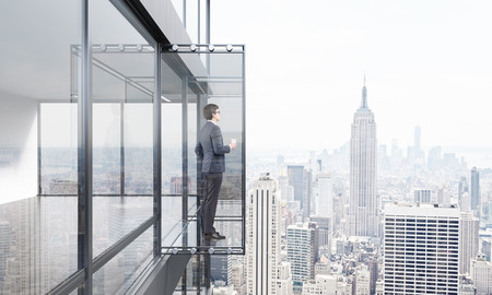 penthouse: Businessman with coffee cup looking into the distance from empty balcony interior on New York city background. 3D Rendering Stock Photo