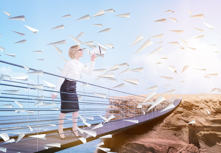 Empresaria rodeada de aviones de papel que se coloca en el puente que lleva al acantilado y que usa el megáfono en fondo del mar y del cielo
