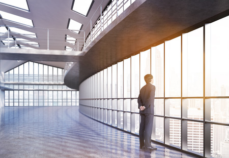 railings: Businessman looking out the window in empty office interior with railings and New York city view. 3D Rendering