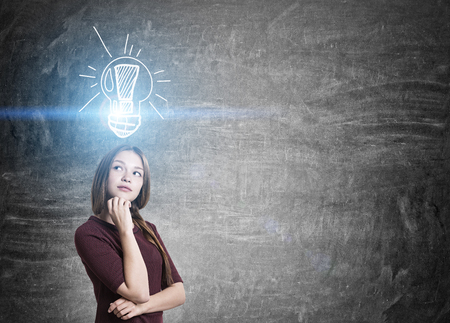 pondering: Idea concept with thoughtful young woman and illuminated light bulb sketch on chalkboard background