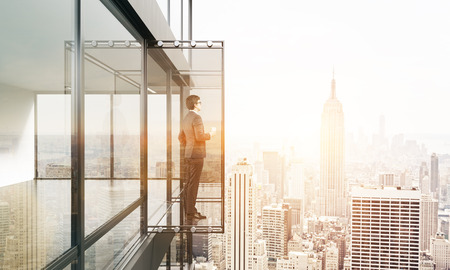 penthouse: Businessman with coffee cup looking into the distance from empty balcony interior on New York city background with sunlight. 3D Rendering Stock Photo