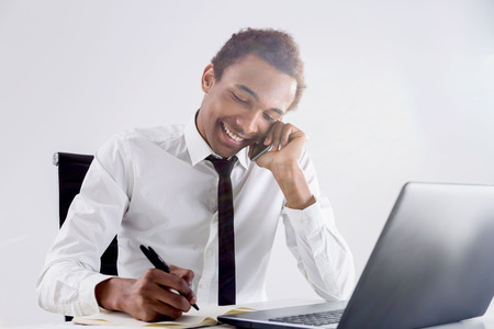 phonecall: Friendly young african american businessman having phone conversation while working at office desk on light background Stock Photo