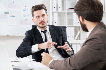 hardworking: Two successful hardworking businessmen discussing something at modern office desk Stock Photo