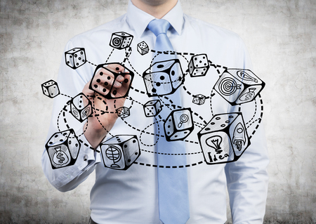 economic theory: Businessman drawing abstract connected dice sketch on concrete background. Game and probability theory Stock Photo