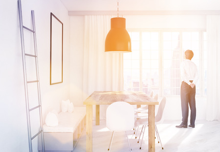 iron curtains: Side view of thoughtful businessman in dining area with table, chairs, iron ladder, bench, picture frame, ceiling lamp and window with curtains and New York city view. Toned image. 3D Rendering
